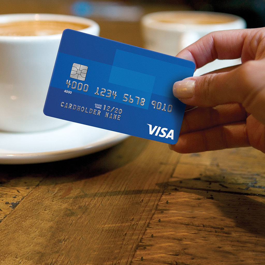 Hand holding Visa Chip card.