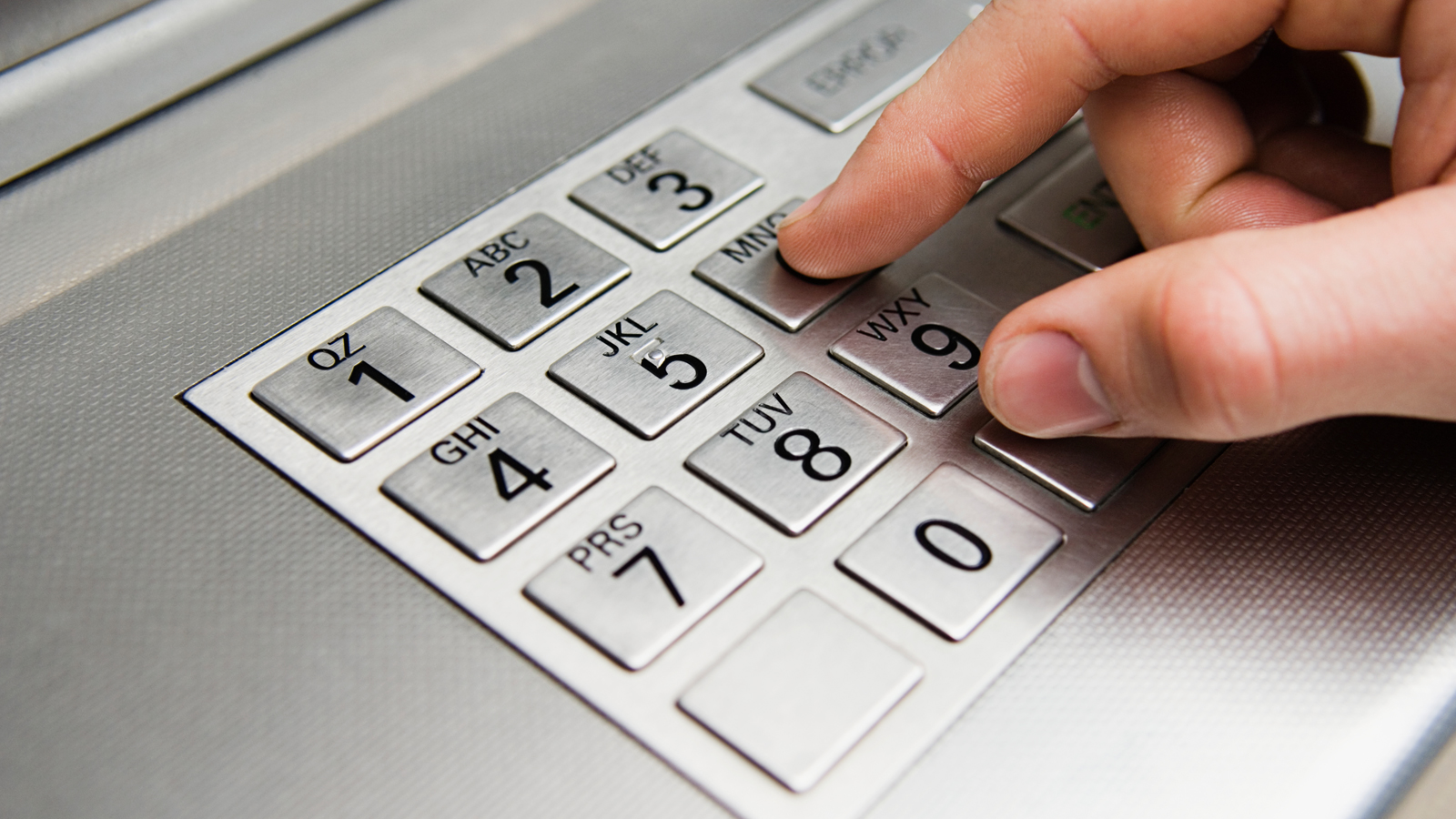 Hand at ATM keyboard.