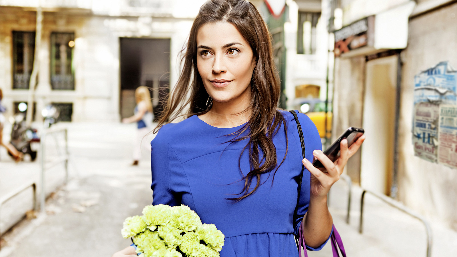 Woman holding a phone and flowers