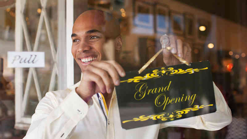 Businessman hanging Grand Opening sign in front window.